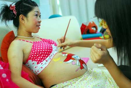 رسامة ترسم على بطن امرأة